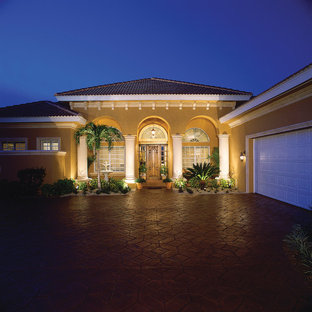 Mid-sized mediterranean beige one-story stucco exterior home idea in Miami with a hip roof
