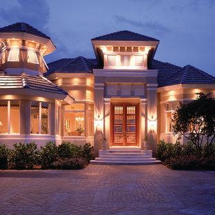 Foto de fachada beige, tropical, grande, de dos plantas, con revestimiento de estuco y tejado a cuatro aguas