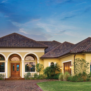 Inspiration for a large mediterranean yellow one-story stucco exterior home remodel in Miami with a hip roof