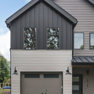 Example of a small country black two-story concrete fiberboard exterior home design in Other with a metal roof