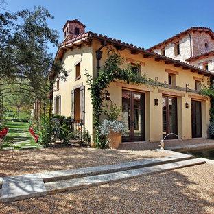Modelo de fachada de casa gris, mediterránea, de tamaño medio, de dos plantas, con tejado a dos aguas, revestimiento de piedra y tejado de teja de barro