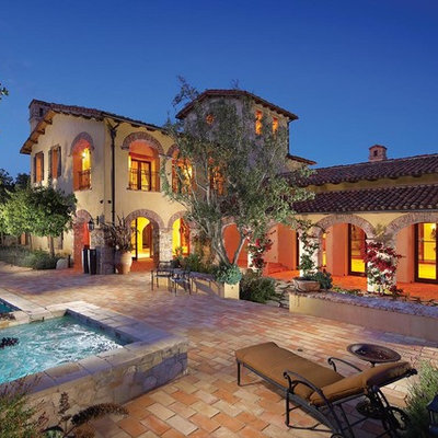 Mid-sized tuscan gray two-story stone exterior home photo in Orange County with a tile roof