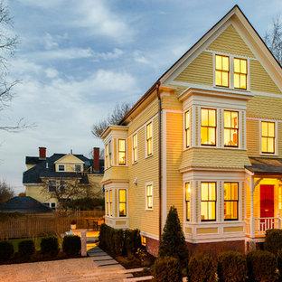 Imagen de fachada amarilla, clásica, de tres plantas, con revestimiento de madera