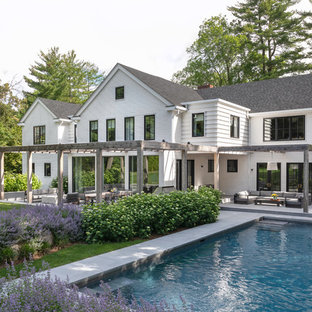 Example of a cottage white two-story exterior home design in New York with a shingle roof