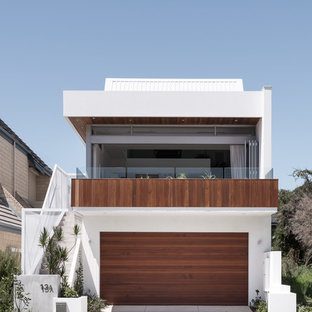 This is an example of a contemporary two-storey white house exterior in Perth with mixed siding, a flat roof and a metal roof.