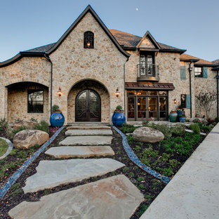 Large tuscan beige two-story stone exterior home photo in Dallas