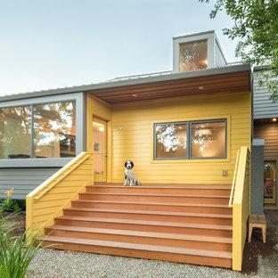 Modelo de fachada de casa amarilla, retro, de dos plantas, con tejado de metal