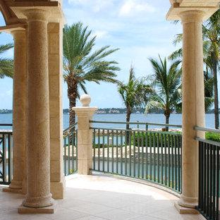 Ejemplo de fachada verde, exótica, extra grande, de dos plantas, con revestimiento de piedra y tejado a dos aguas