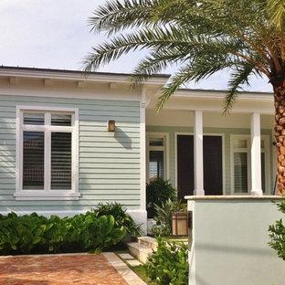 Foto della facciata di una casa verde tropicale a un piano con rivestimento in legno