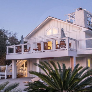 This is an example of a mid-sized beach style two-storey white house exterior in Other with wood siding.