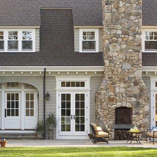 Esempio della facciata di una casa unifamiliare grande grigia classica a due piani con rivestimento in legno e copertura a scandole