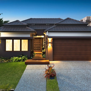 Inspiration for a tropical one-storey stucco grey house exterior in Brisbane with a hip roof and a tile roof.