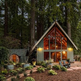 Пример оригинального дизайна: двухэтажный, зеленый частный загородный дом среднего размера в стиле рустика с двускатной крышей и крышей из гибкой черепицы для охотников