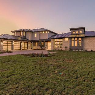 Idéer för att renovera ett mycket stort funkis beige hus, med två våningar, tak i metall och valmat tak