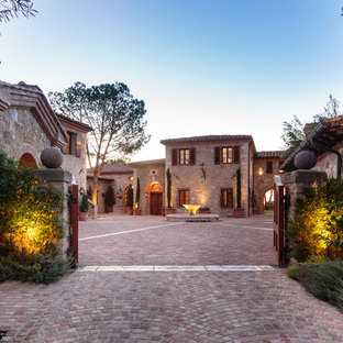 Rustic two-story stone house exterior idea in Orange County with a tile roof