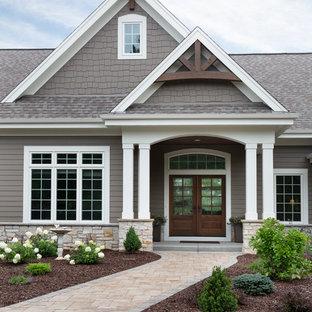 Diseño de fachada de casa marrón, de estilo americano, grande, de una planta, con revestimientos combinados y tejado de varios materiales