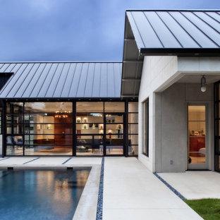 Bild på ett funkis hus, med allt i ett plan, glasfasad och tak i metall