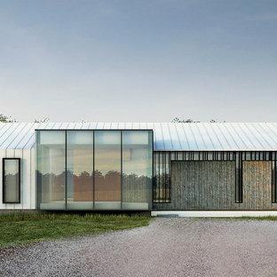 Imagen de fachada blanca, moderna, extra grande, de una planta, con revestimiento de metal y tejado a dos aguas