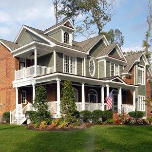 Ejemplo de fachada verde, vintage, grande, de dos plantas, con revestimiento de ladrillo y tejado a dos aguas