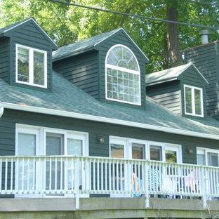 Imagen de fachada de casa verde, clásica, grande, de dos plantas, con revestimiento de madera, tejado a dos aguas y tejado de teja de madera