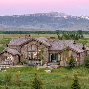 Ispirazione per la facciata di una casa unifamiliare ampia beige rustica a un piano con copertura a scandole, rivestimenti misti e tetto a capanna