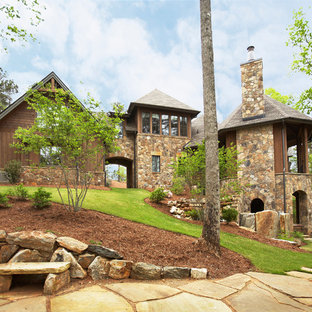 Mountain style brown three-story wood exterior home photo in Other