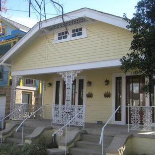 Foto de fachada de casa bifamiliar amarilla, ecléctica, de tamaño medio, de una planta, con revestimiento de madera, tejado a dos aguas y tejado de teja de madera