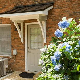Стильный дизайн: маленький, кирпичный, оранжевый частный загородный дом в классическом стиле с односкатной крышей и металлической крышей - последний тренд