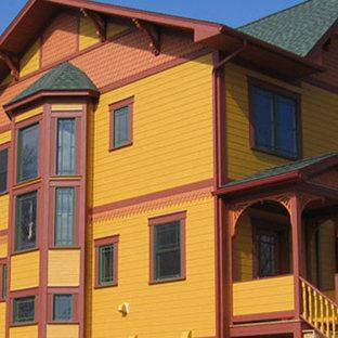 Modelo de fachada amarilla, bohemia, de tamaño medio, de dos plantas, con revestimiento de vinilo y tejado a dos aguas