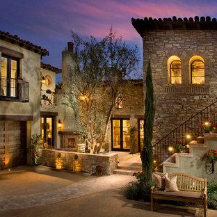 Esempio della facciata di una casa grande mediterranea con rivestimento in pietra