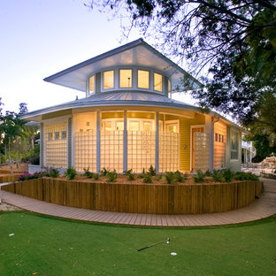 Example of an island style glass exterior home design in Tampa