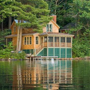 Ejemplo de fachada beige, rural, pequeña, de dos plantas, con revestimiento de madera y tejado a dos aguas