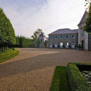 Diseño de fachada de casa beige, moderna, grande, de dos plantas, con revestimiento de hormigón, tejado a dos aguas y tejado de teja de barro