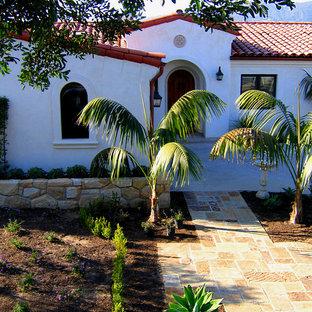 Пример оригинального дизайна: одноэтажный, белый частный загородный дом среднего размера в средиземноморском стиле с облицовкой из цементной штукатурки, полувальмовой крышей и черепичной крышей