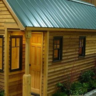 Modelo de fachada marrón, rural, pequeña, de una planta, con revestimiento de madera y tejado a dos aguas