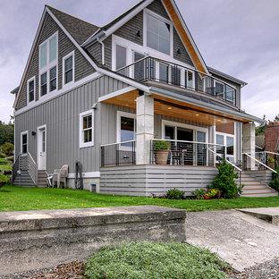 На фото: двухэтажный, серый частный загородный дом среднего размера в морском стиле с двускатной крышей, крышей из гибкой черепицы, серой крышей и отделкой доской с нащельником с