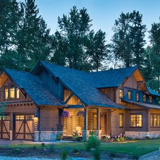 Ejemplo de fachada de casa marrón, rústica, de tamaño medio, de dos plantas, con revestimiento de madera, tejado a dos aguas y tejado de teja de madera
