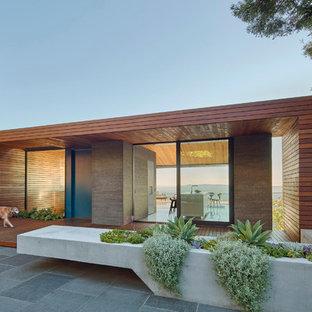 Diseño de fachada marrón, moderna, grande, de una planta, con revestimiento de madera y tejado plano