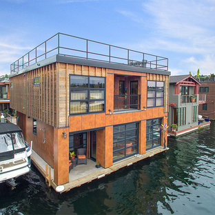 Huge industrial orange two-story wood exterior home idea in Seattle