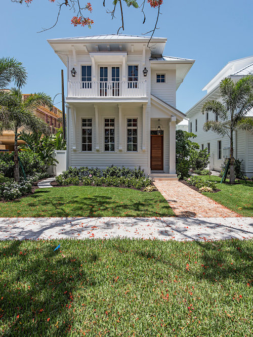 Coastal White Two Story Exterior Home Photo In Miami With A Hip Roof And A