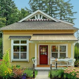 Foto della facciata di una casa unifamiliare piccola gialla american style a due piani con rivestimento con lastre in cemento, tetto a padiglione e copertura a scandole