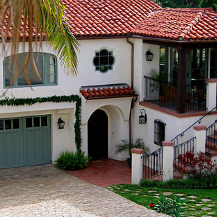 Inspiration for a mid-sized mediterranean white two-story stucco house exterior remodel in Santa Barbara with a hip roof and a tile roof