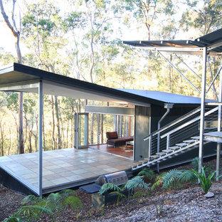 Foto på ett litet funkis svart hus, med metallfasad, allt i ett plan och platt tak