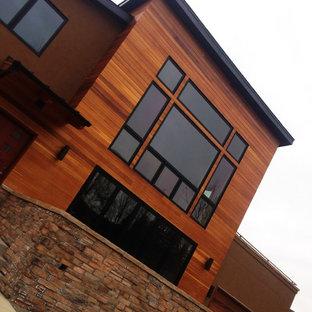Пример оригинального дизайна: огромный, двухэтажный, коричневый частный загородный дом в стиле неоклассика (современная классика) с комбинированной облицовкой