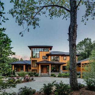 Immagine della facciata di una casa unifamiliare marrone contemporanea a due piani con rivestimento in legno e tetto a padiglione