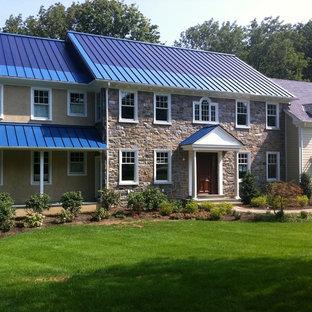 Пример оригинального дизайна: большой, двухэтажный, коричневый дом в классическом стиле с облицовкой из камня, металлической крышей и синей крышей