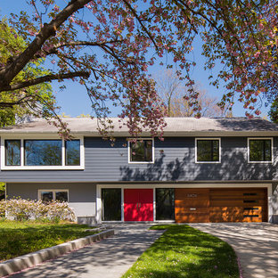 На фото: большой фасад частного дома серого цвета в стиле ретро с разными уровнями, двускатной крышей, комбинированной облицовкой и крышей из гибкой черепицы с