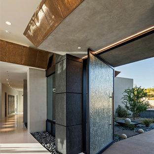 Immagine della facciata di una casa grande beige moderna a un piano con rivestimento in adobe e tetto piano