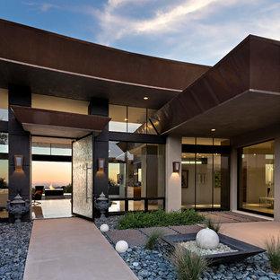 Cette image montre une grand façade de maison beige minimaliste de plain-pied avec un revêtement en adobe et un toit plat.
