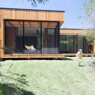 Esempio della facciata di una casa marrone moderna di medie dimensioni con rivestimento in legno e tetto piano
